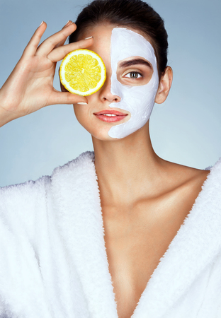 Lovely girl holding a slice of lemon in front of her face and smiling. Photo of girl receiving spa treatments. Beauty & Skin care concept