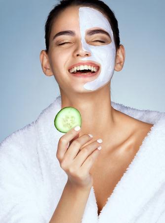 Lachende vrouw met het plakje komkommer in de hand. Foto van grappig meisje met hydraterende gezichtsmasker. Beauty & Skin zorgconcept