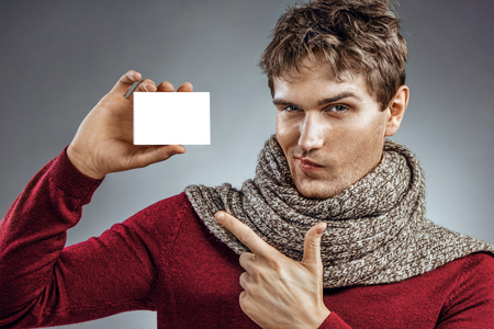 Emotional young man holding box for medicine. Photo of unhealthy man pointing finger at white packaging for medicine. Healthcare concept