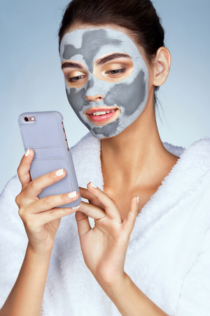 Pretty woman with mask of clay on her face, looks at phone. Photo of girl receiving spa treatments. Grooming himself