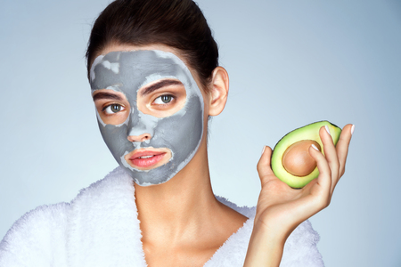 groomed: Attractive girl holding half an avocado in hand. Photo young woman with mask of clay on blue background. Beauty & Skin care concept