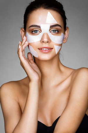 Smiling girl with cotton facial mask. Photo of attractive brunette girl on grey background. Youth and skin care concept