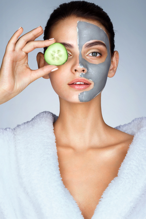 eye mask: Beautiful girl holding a slice of cucumber in front of her face. Photo of girl in white bathrobe and with mask of clay on face. Grooming himself Stock Photo