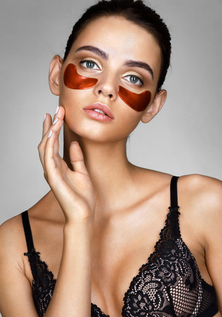 Sensual lady with red eye patches. Portrait of brunette woman touching hand her face. Beauty & Skin care concept