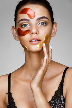 skin color: Attractive woman with color patches on her face. Portrait of young woman touching hand  her face. Skin care concept.