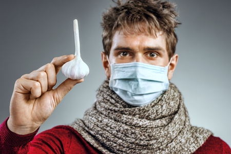 Man in protective mask against infectious diseases and flu. Photo of sick man holding a garlic. Close up. Healthcare concept