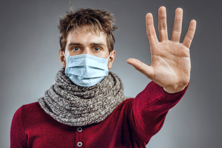 protective mask: Stop - virus! Sick man in protective mask gesturing stop. Healthcare concept