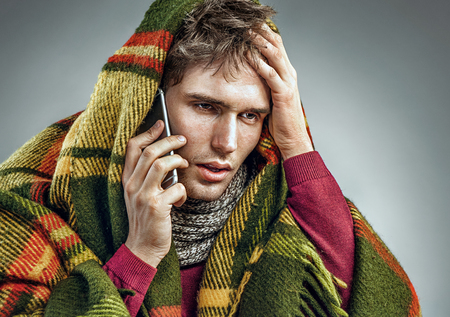 Unhealthy man wrapped in blanket with high temperature calling on the phone. Man suffering cold and winter flu virus Stock Photo