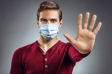 protective mask: Handsome man showing gesture stop. Photo of healthy man wears protective mask against infectious diseases and flu. Health care concept. Stock Photo