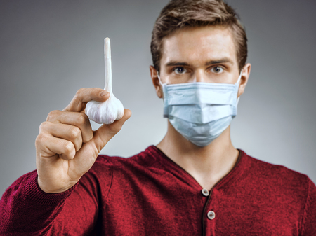 protective mask: Handsome man wears protective mask against infectious diseases and flu. Photo of man holding a garlic. Close up. Healthcare concept
