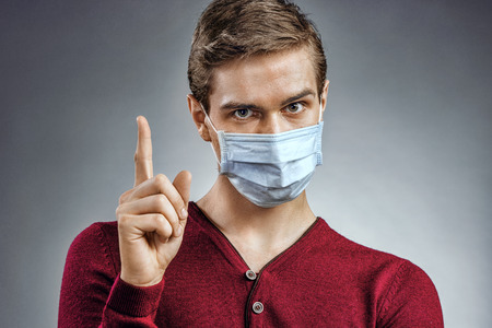 protective mask: Handsome man in protective mask pointing finger up. Health care concept.