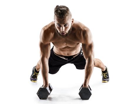 Knappe man doen push ups uit te oefenen met halters. Foto van gespierde man op een witte achtergrond. Kracht en motivatie.