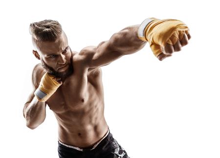 男は獰猛で強力なパンチを投げます。白い背景に分離された筋肉の男の写真。強さと動機。