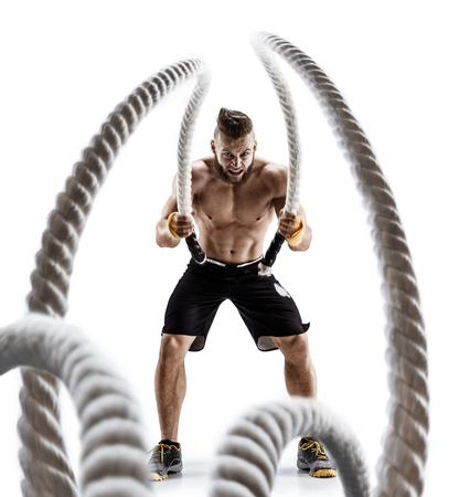 魅力的な筋肉男が重いロープでワークアウトします。スポーツウェアは、白い背景で隔離のハンサムな男の写真。Crossfit