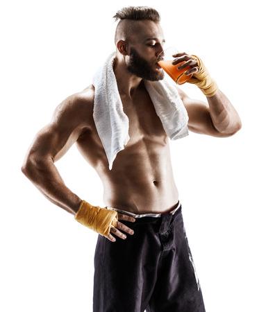 Rusttijd. Knappe jonge man in sportkleding met handdoek op zijn schouders en drinkt sap