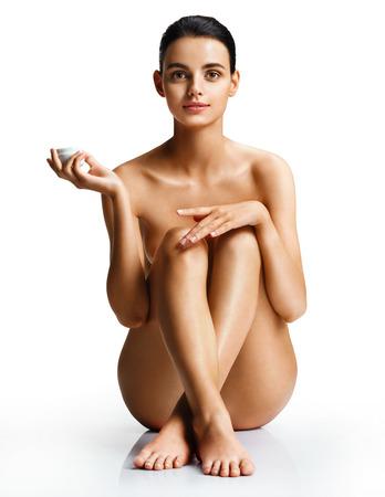 fille sexy nue: Jeune femme nue appliquant une crème hydratante assise sur fond blanc. Photo de belle femme avec une peau parfaite. Concept de soins de la peau Banque d'images