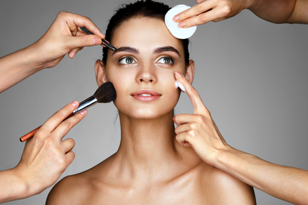 Smiling girl surrounded by hands of makeup artists with brushes,cotton sponge and moisturizer cream near her face. Photo of beautiful woman on gray background. Grooming himself