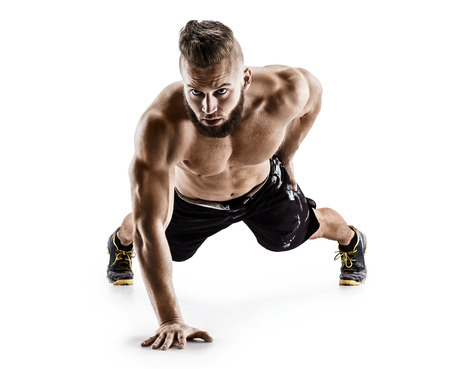 Sporty man doing push-ups exercises from the floor on the right arm. Photo muscular man isolated on white background. The strength and motivation