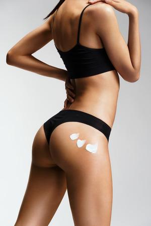 cuerpo femenino: Aplicación de crema hidratante. Slim girl en lencería negra se preocupa por sus nalgas. Parte de la belleza del cuerpo femenino. Concepto de cuidado de la piel