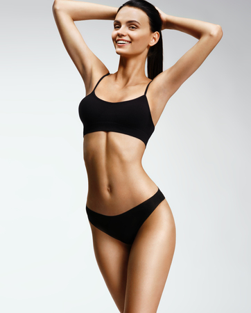 Laughing sporty girl in black bikini posing on grey background. Photo of attractive girl with slim toned body. Beauty and body care concept Standard-Bild