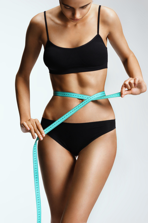 Slim girl in black lingerie with a ribbon measures the size of the waist. Beautiful part of female body. Fitness or body care concept Stock Photo