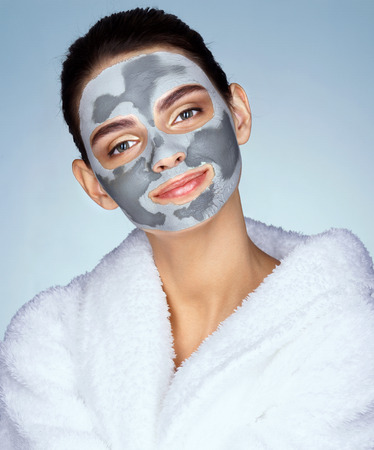 Charming young girl with mask of clay on her face. Photo of happy girl receiving spa treatment on blue background. Beauty & Skin care concept