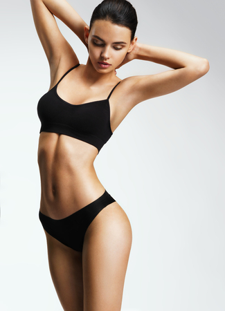 Attractive sporty woman in black bikini posing on grey background. Photo of brunette woman with slim toned body. Beauty and body care concept