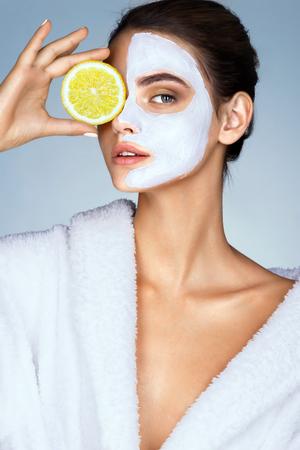 그녀의 얼굴의 앞에 레몬 슬라이스를 들고 갈색 머리 여자. 얼굴 마스크 보습 여자의 사진입니다. 뷰티 & 스킨 케어 개념