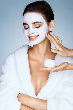 Smiling girl with moisturizing facial mask and hands of the beautician. Photo of beautiful stylish girl receives the spa treatments. Beauty & Skin care concept