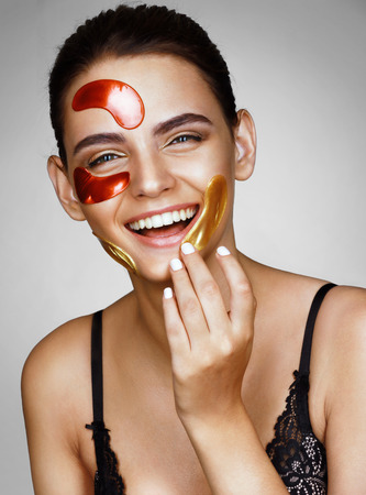 skin color: Laughing charming woman with color patches on her face. Photo of young woman touching hand  her face. Skin care concept