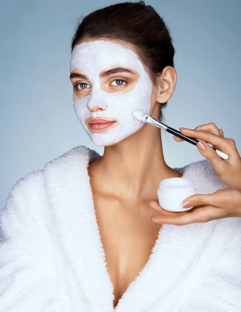 Young woman with moisturizing facial mask and hands of the beautician. Photo of  pretty woman receives the spa treatments. Beauty & Skin care concept Stok Fotoğraf