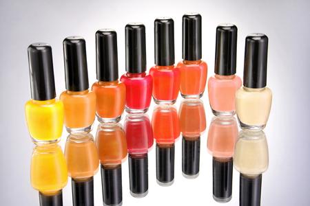 Bottles of colorful nail polish on grey background. Close up.