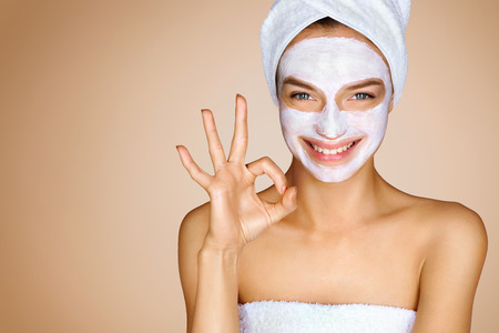 Funny young girl with moisturizer cream mask showing gesture okay. Photo of girl with towel on her head on beige background. Youth and Skin Care Concept