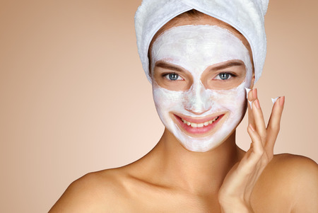 Young woman applying moisturizer cream on her face. Photo of smiling woman receiving spa treatments. Grooming himself Stock Photo