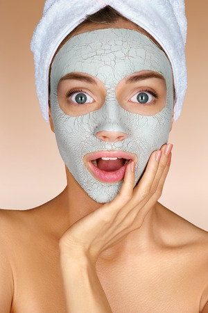 OMG! Pretty girl in shock. Photo of girl with towel on her head and clay facial mask on beige background. Skin care concept