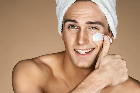 Knappe jonge man die room toepast op zijn gezicht. Portret van een slimme man met perfecte huid. Huid zorgconcept Stockfoto