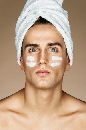 Young man with moisturizer on the face. Photo of handsome man with perfect skin. Beauty & Skin care concept