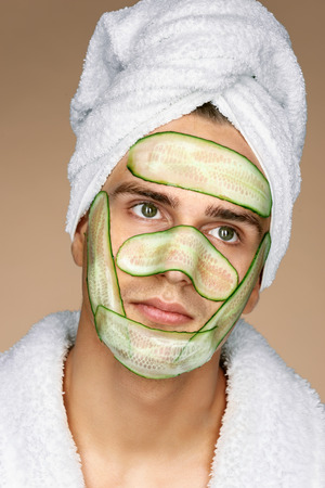 Fashionable man receiving facial mask of cucumber. Cosmetic procedure mans face. Grooming himself Stock Photo
