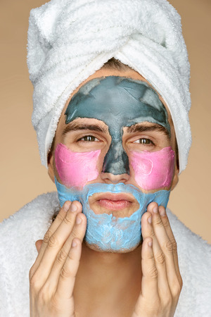Enthusiastic man applies a face mask. Photo of man in towel with different face masks on his face. Beauty & Skin care concept