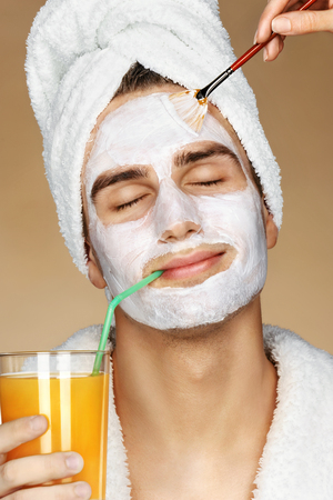 Handsome man getting a facial treatment. Beautician is applying facial cream on his skin. Beauty & Skin care concept