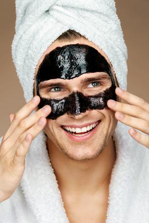 顔に黒いマスクを持つ幸せな男。スパの治療を受けてよく手入れをされた男性の写真。美容・ スキンケア コンセプト