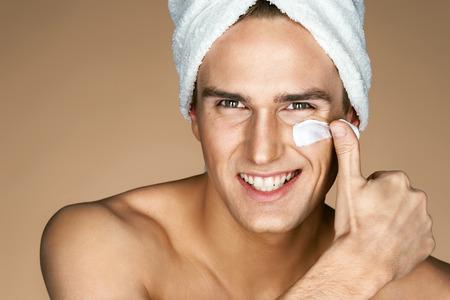 Jonge man room toe te passen op zijn gezicht. Portret van glimlachende man met perfecte huid. Huidverzorging concept