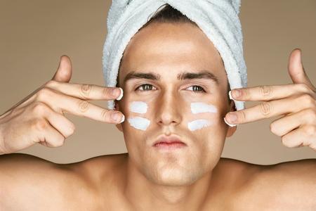 얼굴에 로션을 가진 심각한 남자. 완벽 한 피부를 가진 남자의 사진입니다. 스스로 정리하기