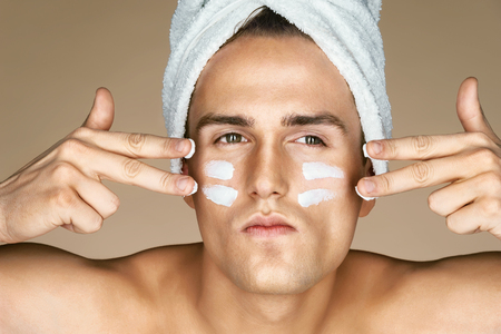 Ernstige man met vochtinbrengende crème op het gezicht. Foto van man met perfecte huid. Zichzelf verzorgen