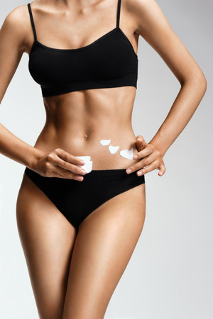 body shape: Applying moisturizer cream.  Sporty woman in black lingerie cares about her belly. Beauty part of female body. Womans shape with clean skin. Skin care concept Stock Photo