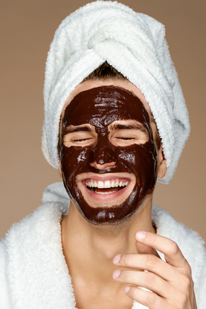 Laughing man with chocolate facial mask. Photo of well groomed man receiving spa treatments. Beauty & Skin care concept