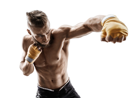 Athletic boxer throwing a fierce and powerful punch. Photo of muscular man isolated on white background. Strength and motivation. Stock Photo