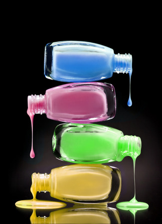 Cosmetic nail polish dripping from open bottles on black background. Close up
