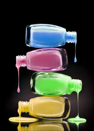 Kosmetisch nagellak dat van open flessen op zwarte achtergrond druipt. Detailopname