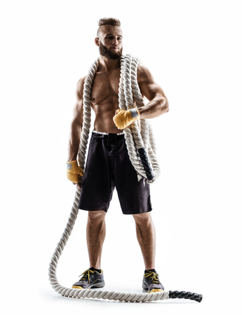 Athletic man with heavy ropes on his shoulders. Photo of young man in sportswear isolated on white background. Strength and motivation.